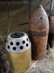 13. Pocisk moździerza 210 mm a przy nim łuska z perforowaną pokrywką.
