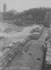 Zdjęcie z włoskich wykopalisk na wyspie z roku 1942. Przedstawia odkopane podstawy starożytnych murów obronnych. W głębi strzelista wieża wybudowanego na wyspie w końcu lat dwudziestych kościoła katolickiego dell'Agnus Dei.