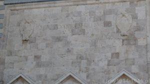 """Na ścianie Palazzo del Governo od strony palatanu Hipokratesa zachowała się łacińska sentencja """"Legum omnes servi sumus"""", czyli """"Wszyscy jesteśmy sługami prawa"""" i służy teraz nowej władzy. Herb po prawej został skuty. (Isola Coo)"""