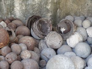 Wśród starożytnych kul armatnich hełmy włoskie i brytyjskie. (Isola Coo)