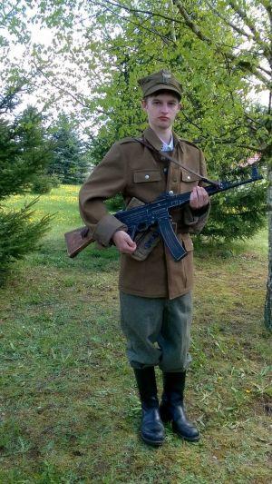 """Podlasie maj 1946r. Jeden z najmłodszych partyzantantów 5 Wileńskiej Brygadzie AK. W oddziałach majora """"Łupaszki"""" służyło kilku kilkunastoletnich chłopaków. Widoczna rogatywka wz.43, (zbyt duża ) bluza wz.36, spodnie niemieckie M43, saperki niemieckie, pożyczony od starszych stażem i wiekiem partyzantów specjalnie do zdjęcia niemiecki karabinek szturmowy MP43"""