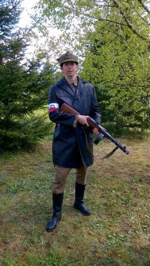 """Podlasie, maj 1945. Milicjant. Płaszcz skórzany z biało-czerwoną opaską i literami MO, pod płaszczem mundur wz.43. na głowie rogatywka wz.43. z orłem tzw. """"kuricą"""", w rękach pistolet maszynowi prod. sowieckiej PPSz wz.41"""