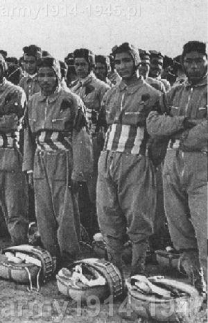 """Libijscy spadochroniarze we włoskiej służbie, czyli """"Ascari del Cielo"""". Na brzuchu nosili charakterystyczny szeroki pas fascia distintiva RCTC (Regi Corpi Truppe Coloniali – Królewskiego Korpusu Wojsk Kolonialnych) w pionowe niebiesko-białe pasy. U ich stóp spadochrony Salvator D37. (Wikipedia)"""