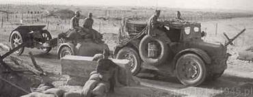 Haubica 100/17 mod.914 TM, holowana za zdobyczną przyczepą amunicyjną przez ciągnik TL37 w marszu w rejonie Tobruku.