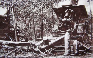 15. 21 cm Mörser M. 10, przy nim pociski i łuska z zagadkową perforowaną pokrywką. Duże ilości takich perforowanych obiektów jest odkopywanych przy starych stanowiskach działa 210 mm.