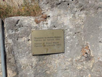 """34. Tabliczka informacyjna na bastei oznaczonej na planie nr 2, informująca o nazwie """"Del Carretto Bastion"""" nadanej bastei na cześć wielkiego mistrza Fabrizio del Carretto (wielki mistrz w latach 1513-1521)."""