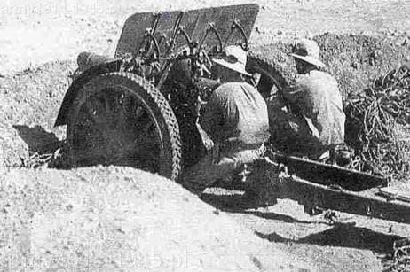 Rok 1941 - Afryka Północna. Żołnierze obsługują haubicę 100/17 mod.914 TM (z metalowymi kołami z ogumieniem typu masyw).